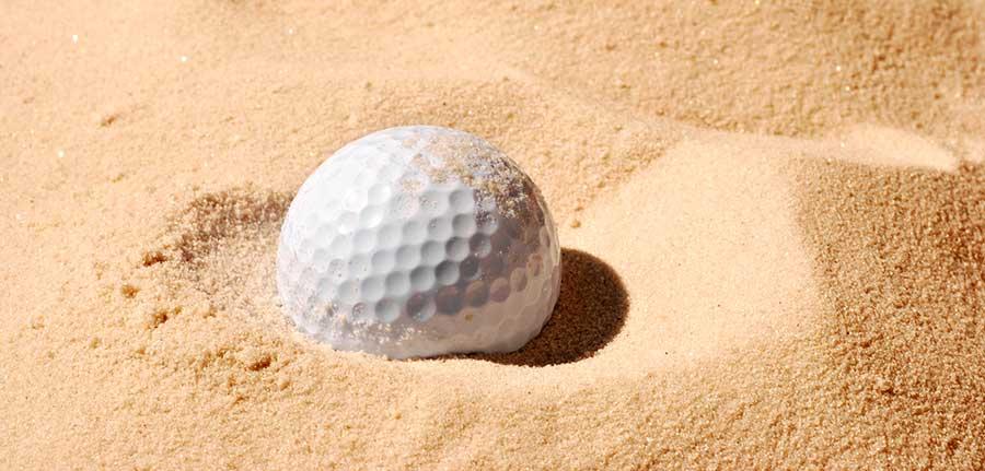 Pelota de golf atrapada en un bunker